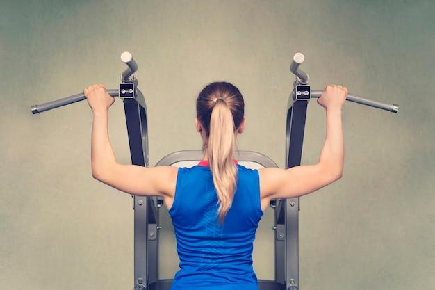 Mulher sexy apta realizando flexões em um bar. treinamento pesado. visão traseira. loira em uma camiseta azul é puxada para cima na barra transversal. aparelhos de treino desportivo para pull-ups.