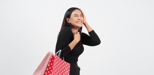 Mulher sexy às compras. linda garota de preto segurando sacolas vermelhas isoladas sobre o branco