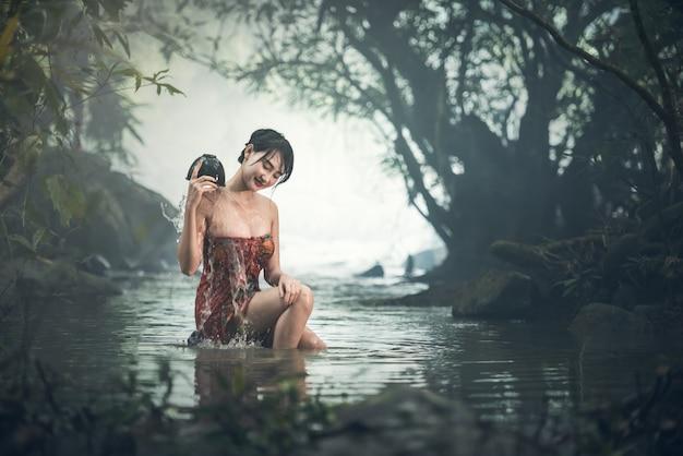 Mulher sexy asiática tomando banho no riacho, tailândia