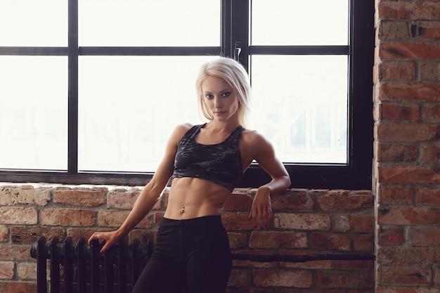 Mulher sexy atleta musculoso posando na janela
