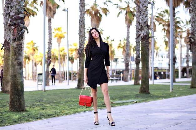 Mulher sexy atraente confiante andando pela rua com palms, empresária moderna vestido preto minimalista, viajando para a espanha.