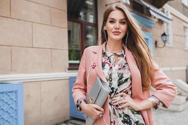 Mulher sexy atraente e sorridente caminhando pelas ruas da cidade com casaco rosa, tendência da moda de primavera, segurando a bolsa, ouvindo música em fones de ouvido