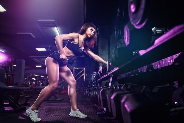 Mulher sexy atraente em forma no ginásio se agacha com uma barra. mulher treinando de volta. fumaça colorida