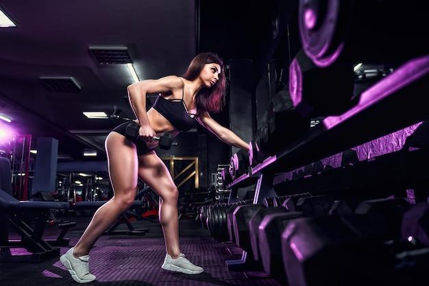 Mulher sexy atraente em forma no ginásio se agacha com uma barra. mulher treinando de volta.