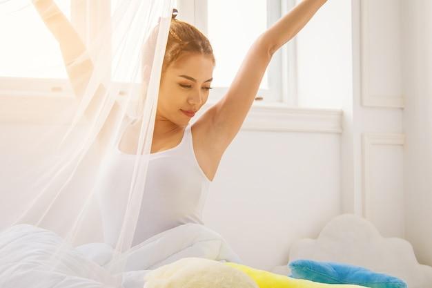 Mulher sexy atrás de rede slim ao lado da janela acordar e relaxar na manhã