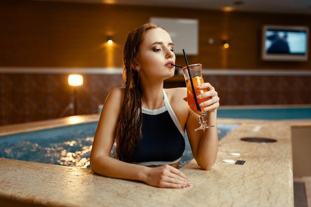Mulher sexy bebe coquetel de frutas à beira da piscina