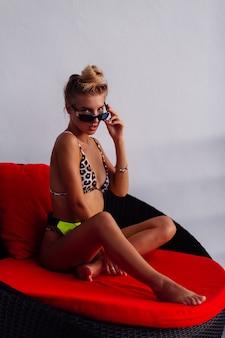 Mulher sexy, bronzeada, de moda europeia, blogueira em minúsculo biquíni leopardo, bolsa de cintura verde amarelo neon em sofá-travesseiro vermelho