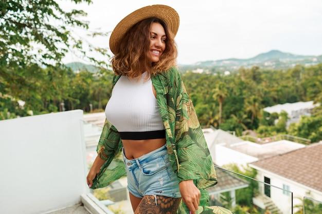 Mulher sexy com cabelos cacheados, posando na varanda com vista incrível.