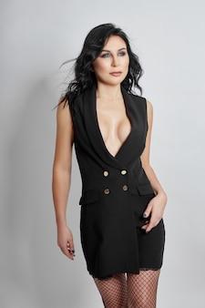 Mulher sexy com corpo perfeito e seios grandes posando em um fundo cinza