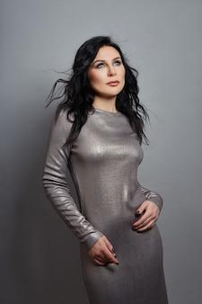 Mulher sexy com figura perfeita e seios grandes, posando em uma parede cinza