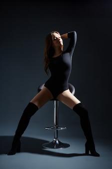 Mulher sexy com pernas longas e cabelo posando em um fundo escuro. olhos bonitos e pele lisa e limpa