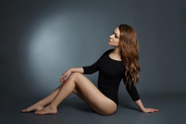 Mulher sexy com pernas longas e cabelo posando em um fundo escuro. olhos lindos e pele limpa e lisa