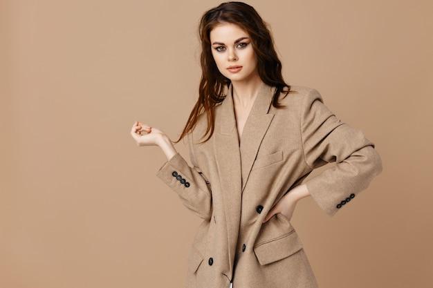 Mulher sexy com um casaco em um fundo bege fazendo gestos com as mãos