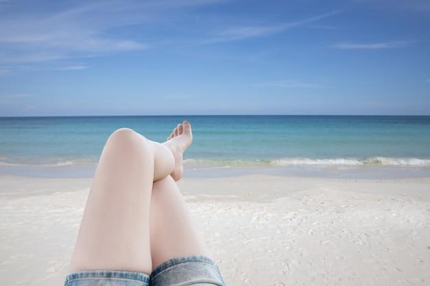 Mulher sexy com uma perna deitada e relaxando na praia