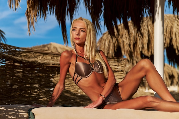Mulher sexy de biquíni sentada numa espreguiçadeira sob o guarda-sol de palha na praia