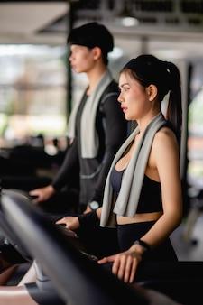 Mulher sexy de foco seletivo em roupas esportivas, correndo na esteira, homem bonito borrado, quase correndo, eles estão se exercitando em um moderno ginásio de fitness, copie o espaço