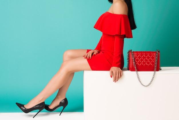 Mulher sexy de salto alto com bolsa vermelha sobre fundo azul.