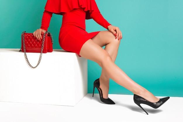 Mulher sexy de salto alto com bolsa vermelha