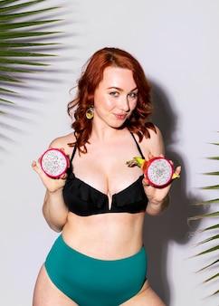Mulher sexy de sutiã segurando frutas fatiadas de dragão