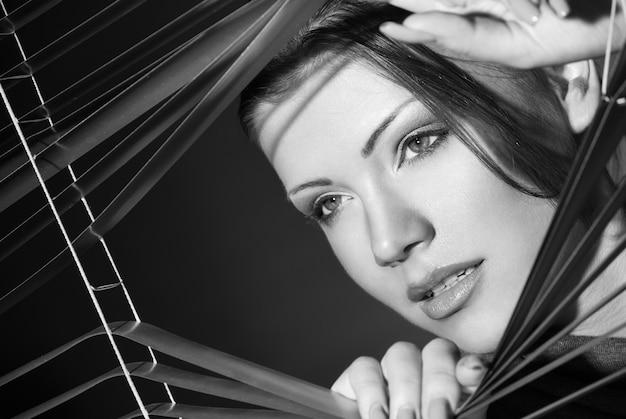 Mulher sexy de vestido preto com persianas