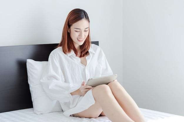 Mulher sexy desgaste camisa branca jogar jogo no tablet e sorrir na cama
