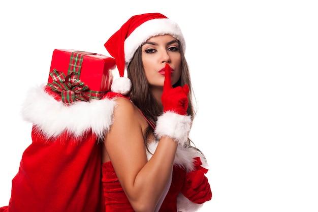 Mulher sexy do papai noel com saco de natal dizendo shh