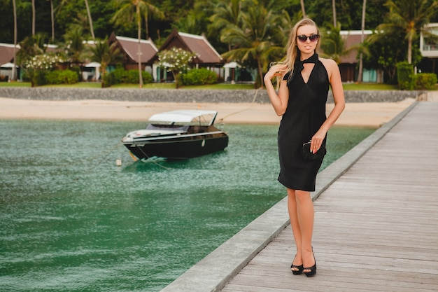 Mulher sexy e atraente luxuosa vestida de vestido preto, posando no cais em um hotel resort de luxo, usando óculos escuros, férias de verão, praia tropical