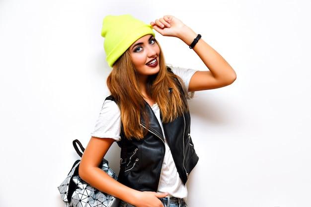 Mulher sexy e deslumbrante da moda posando perto de uma parede branca, estilo de rua moderno, colete de couro de motociclista, shorts curtos de néon, mochila e chapéu de néon, corpo sexy bronzeado de git, yo, muamba, verão, flash, engraçado, louco
