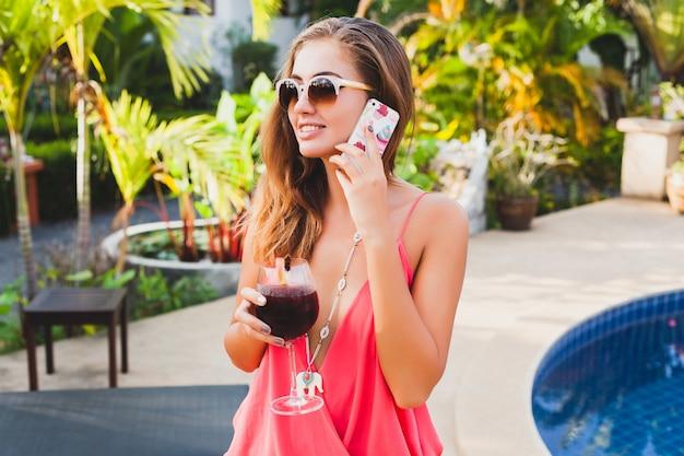 Mulher sexy e elegante em roupa de festa da moda nas férias de verão com um copo de coquetel se divertindo na piscina falando ao telefone