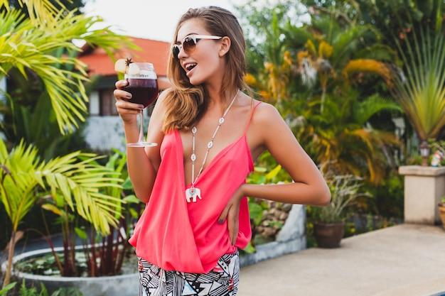 Mulher sexy e elegante em roupa de festa da moda nas férias de verão com um copo de coquetel se divertindo na piscina