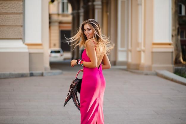 Mulher sexy elegante atraente com vestido rosa verão sexy cabelo comprido andando na rua segurando bolsa
