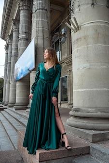Mulher sexy elegante com vestido verde longo posando perto da coluna do teatro da cidade