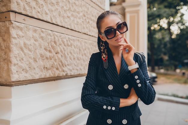 Mulher sexy elegante vestida com um terno de smoking elegante andando pela cidade no dia de primavera de verão