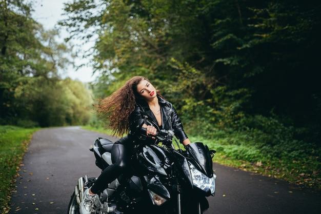 Mulher sexy em calça de couro preta sentada em uma motocicleta esportiva preta