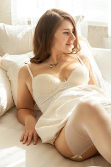 Mulher sexy em lingerie deitada na cama em um dia de sol