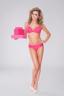 Mulher sexy em lingerie e presentes rosa