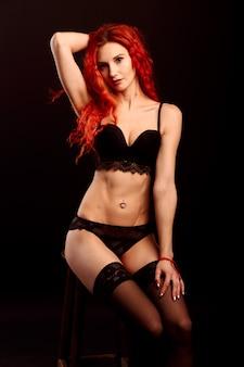 Mulher sexy em lingerie em fundo preto, cabelo ruivo
