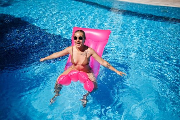 Mulher sexy em óculos de sol, descansando e tomando banho de sol em um colchão rosa na piscina. mulher jovem em biquíni bege flutuando em um colchão inflável rosa