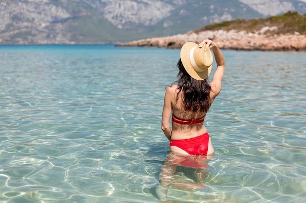 Mulher sexy em pé na água do mar