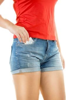 Mulher sexy em shorts posando com preservativo embalado