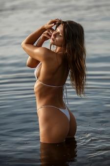 Mulher sexy em traje de banho na margem do rio