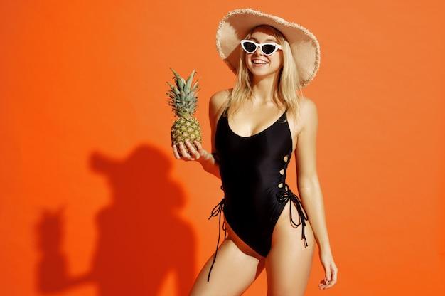 Mulher sexy em traje de banho posa com abacaxi na cor laranja
