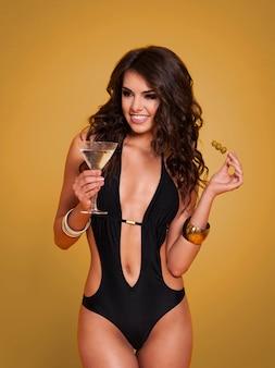 Mulher sexy em trajes de banho bebendo martini