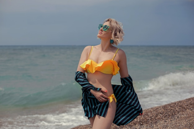 Mulher sexy em um maiô amarelo, uma camisa verde listrada e óculos de sol sentada na praia à beira-mar no verão