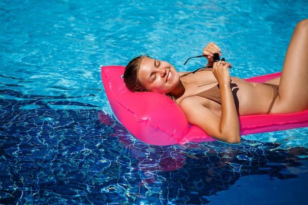 Mulher sexy em um maiô encontra-se em um colchão inflável rosa na piscina. relaxe à beira da piscina em um dia quente e ensolarado de verão. conceito de férias
