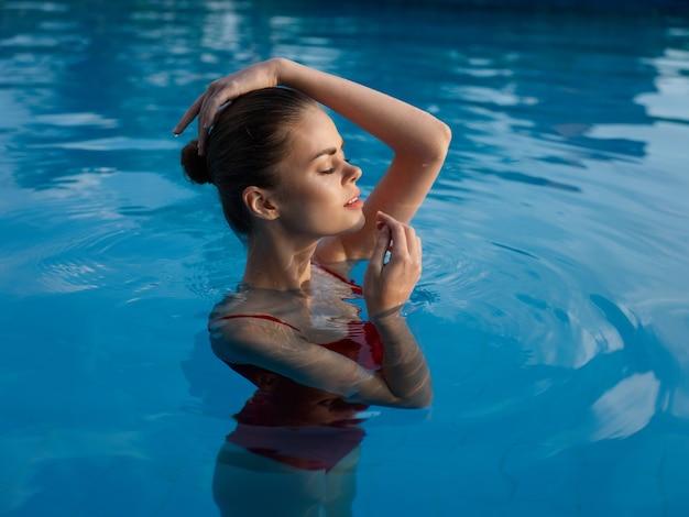 Mulher sexy em um maiô nada em água transparente e toca a cabeça com as mãos