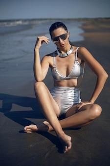 Mulher sexy em um maiô prateado e óculos escuros sentada na praia no verão