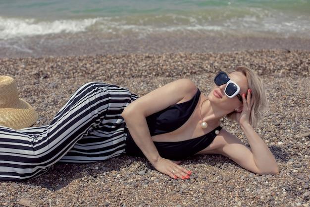 Mulher sexy em um maiô preto, calça listrada e óculos de sol deitada na praia à beira-mar no verão