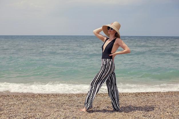 Mulher sexy em um maiô preto, calça listrada e óculos escuros caminhando na praia
