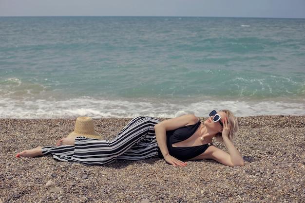 Mulher sexy em um maiô preto, calça listrada e óculos escuros deitada na praia